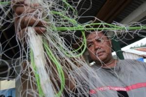 Buhari memperbaiki jaring penangkap ikan miliknya (Jim Holmes/Oxfam)