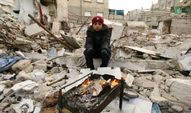 Seorang anak di Gaza mencoba menghangatkan tubuh di musim dingin diantara reruntuhan bangunan (dok. oxfam.org.uk)