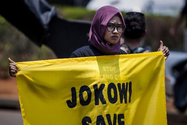 Salah seorang warga Batang membentangkan spanduk meminta Presiden Jokowi menyelamakan petani dan nelayan Batang lewat pembatalan proyek PLTU Batang (dok. greenpeace)