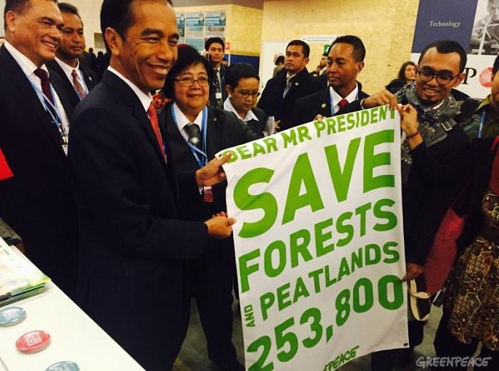 Presiden Joko Widodo menerima banner imbuauan untuk menyelamatkan hutan dan gambut dari aktivis Greenpeace (dok. greenpeace)