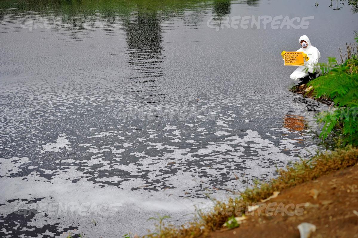 """Aktivis Greenpeace memegang papan bertuliskan: """"Apakah anda siap melawan pembuangan limbah beracun?"""" (dok. greenpeace/yudi mahatma)"""