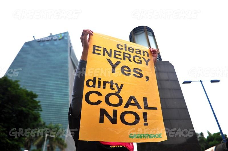 Aktivis Greenpeace membentangkan poster protes terhadap Adaro terkait pembangunan PLTU Batang (ok. greenpeace)