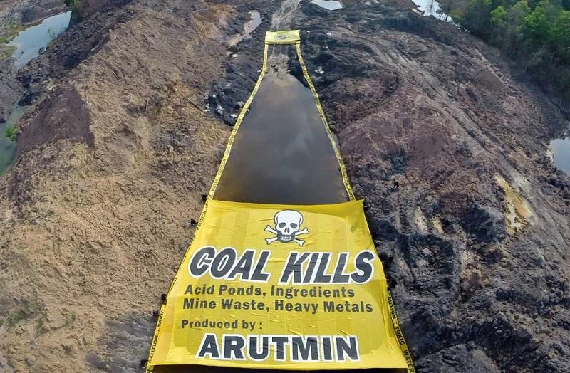 Aktivis Greenpeace melakukan aksi membentangkan peringatan bahaya air beracun di bekas pengerukan tambang batubara, Asam-Asam, Kalimantan Selatan. (dok. greenpeace)
