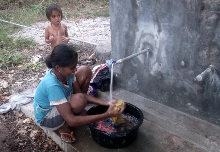 Seorang ibu warga dusun Kambo Umah, Sumba Timur, NTT mencuci pakaian dengan air dari sumur bor bertenaga matahari (dok. rahmat adinata)