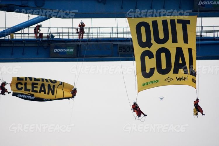 Aktivis Greenpeace Indonesia menuruni crane membentangkan poster besar seruan hentikan batubara (dok. greenpeace)