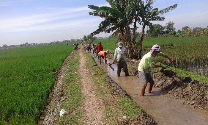 Membersihkan sampah yang menyumbat saluran irigasi (dok. villagerspost.com/tim jurnalis desa kalensari)